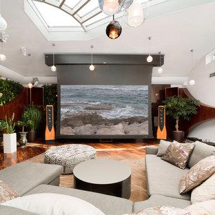 Пример оригинального дизайна интерьера: изолированный домашний кинотеатр в стиле фьюжн с белыми стенами, паркетным полом среднего тона и экраном для проектора