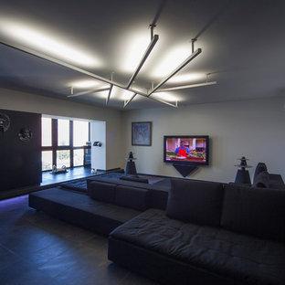 Idee per un grande home theatre minimal aperto con pareti bianche, pavimento in ardesia, TV a parete e pavimento nero
