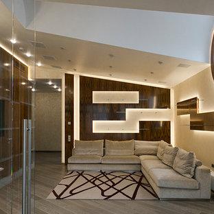 Idee per un home theatre contemporaneo di medie dimensioni e aperto con pareti beige, pavimento in legno verniciato, TV a parete e pavimento grigio