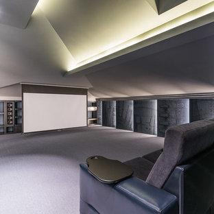 Пример оригинального дизайна интерьера: большой изолированный домашний кинотеатр в современном стиле с серыми стенами, полом из коврового покрытия и экраном для проектора