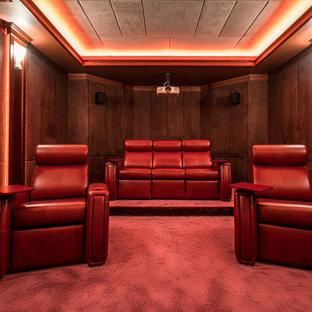 На фото: изолированный домашний кинотеатр в современном стиле с коричневыми стенами, ковровым покрытием и красным полом с