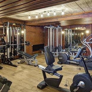 Неиссякаемый источник вдохновения для домашнего уюта: домашний тренажерный зал в стиле кантри с тренажерами, коричневыми стенами, паркетным полом среднего тона и коричневым полом