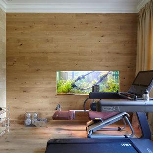 Неиссякаемый источник вдохновения для домашнего уюта: тренажерный зал в современном стиле с коричневыми стенами и паркетным полом среднего тона