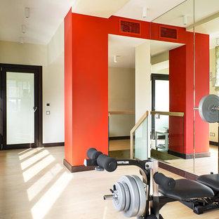 Foto di una sala pesi design con pareti multicolore, pavimento in legno massello medio e pavimento beige