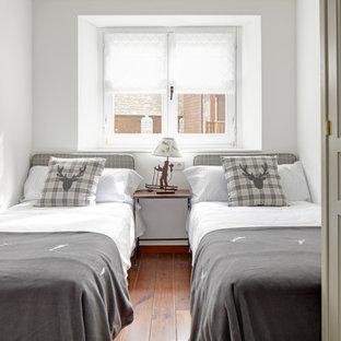 Modelo de dormitorio infantil clásico renovado, pequeño, con paredes blancas, suelo de madera en tonos medios y suelo marrón