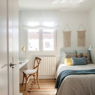 Diseño de dormitorio infantil escandinavo con paredes blancas, suelo de madera en tonos medios y suelo marrón