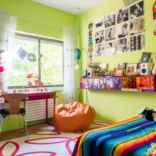 Ispirazione per una cameretta per bambini da 4 a 10 anni bohémian di medie dimensioni con pareti verdi e pavimento in legno massello medio