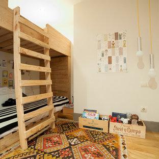 Foto di una piccola cameretta per bambini da 4 a 10 anni scandinava con pareti beige, pavimento in legno massello medio e pavimento beige