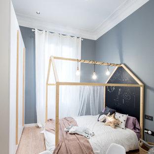 Ejemplo de dormitorio infantil de 4 a 10 años, escandinavo, con paredes azules, suelo de madera clara y suelo beige