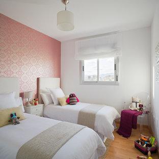 Ejemplo de dormitorio infantil actual con paredes rosas, suelo de madera clara y suelo beige