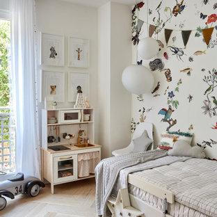 Modelo de dormitorio infantil contemporáneo con paredes multicolor, suelo de madera clara y suelo beige