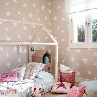 Foto på ett stort skandinaviskt barnrum kombinerat med sovrum, med rosa väggar, laminatgolv och brunt golv