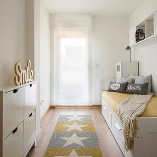 Imagen de dormitorio infantil nórdico con paredes blancas, suelo de madera en tonos medios y suelo marrón