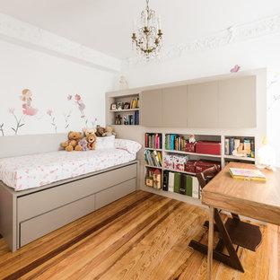 Diseño de habitación de niña de 4 a 10 años, actual, con paredes blancas, suelo de madera en tonos medios y suelo marrón
