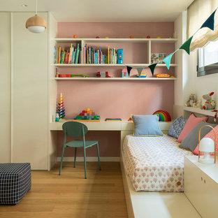 Ejemplo de dormitorio infantil de 4 a 10 años, actual, grande, con paredes rosas, suelo de madera en tonos medios y suelo marrón