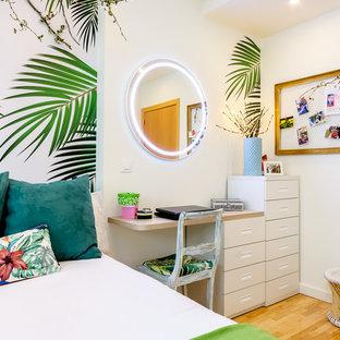 Modelo de dormitorio infantil tropical con paredes multicolor, suelo de madera en tonos medios y suelo beige