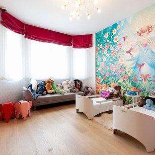 Ejemplo de dormitorio infantil de 1 a 3 años, actual, grande, con paredes multicolor y suelo de madera clara