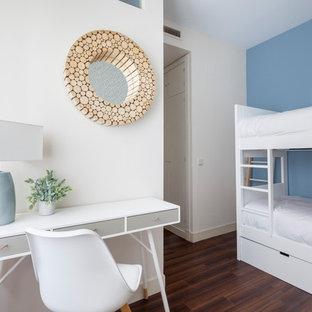 Imagen de dormitorio infantil costero con paredes azules, suelo de madera oscura y suelo marrón