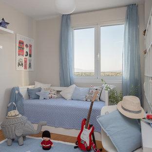 Imagen de dormitorio infantil de 1 a 3 años, marinero, con paredes grises y suelo de madera en tonos medios