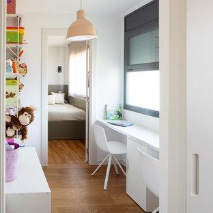 Diseño de habitación infantil unisex contemporánea con escritorio, paredes blancas, suelo de madera en tonos medios y suelo marrón
