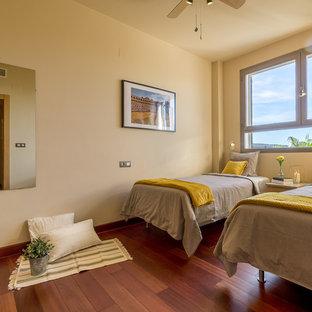 Immagine di una cameretta per bambini mediterranea di medie dimensioni con pareti beige, pavimento in laminato e pavimento marrone