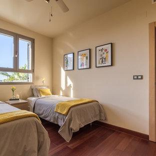 Foto di una cameretta per bambini mediterranea di medie dimensioni con pareti beige, pavimento in laminato e pavimento marrone