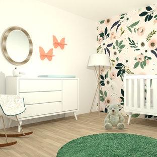 Ispirazione per una cameretta per bambini da 1 a 3 anni bohémian di medie dimensioni con pareti rosa, pavimento in laminato, pavimento marrone e carta da parati