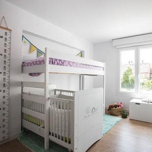 Ejemplo de dormitorio infantil de 1 a 3 años, actual, con paredes blancas, suelo de madera en tonos medios y suelo marrón