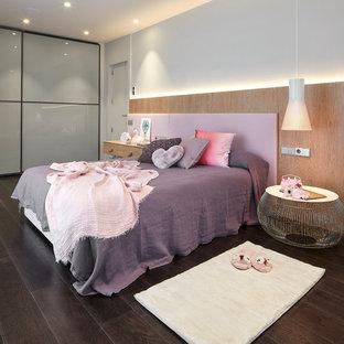Modelo de dormitorio infantil contemporáneo con paredes blancas, suelo de madera oscura y suelo marrón