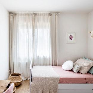 Imagen de dormitorio infantil de 4 a 10 años, escandinavo, pequeño, con paredes blancas, suelo de madera en tonos medios y suelo beige