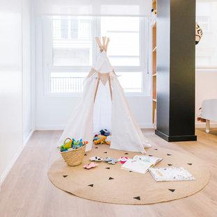 Imagen de dormitorio infantil de 1 a 3 años, nórdico, de tamaño medio, con paredes blancas, suelo de madera en tonos medios y suelo marrón