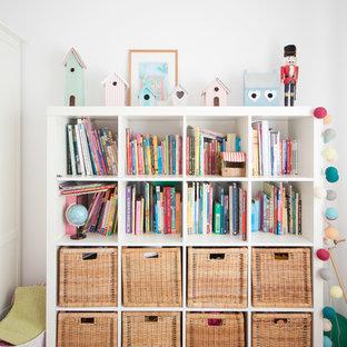Modelo de habitación de niña de 4 a 10 años, contemporánea, de tamaño medio, con suelo de madera clara, suelo beige, escritorio y paredes blancas