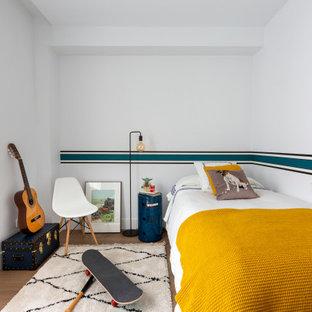 Modelo de dormitorio infantil contemporáneo, de tamaño medio, con paredes blancas y suelo marrón