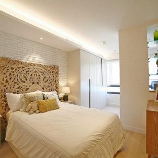 Diseño de dormitorio infantil contemporáneo con paredes blancas, suelo de madera clara y suelo beige