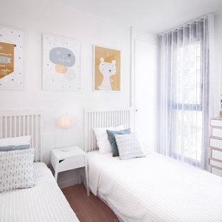 Imagen de dormitorio infantil de 4 a 10 años, clásico renovado, de tamaño medio, con paredes blancas y suelo de madera en tonos medios