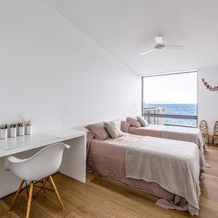 Imagen de dormitorio infantil marinero con paredes blancas, suelo de madera en tonos medios y suelo marrón