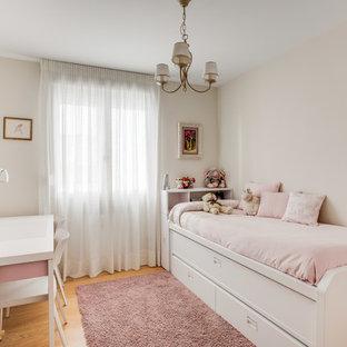 Diseño de dormitorio infantil tradicional renovado con paredes beige, suelo de madera en tonos medios y suelo marrón
