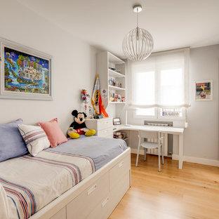 Modelo de dormitorio infantil tradicional renovado con paredes grises, suelo de madera en tonos medios y suelo marrón
