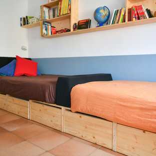 Minimalistisk inredning av ett könsneutralt barnrum kombinerat med sovrum och för 4-10-åringar, med blå väggar och klinkergolv i terrakotta