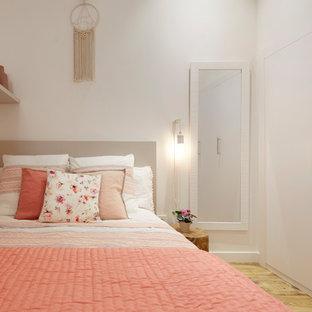 Imagen de dormitorio infantil escandinavo con paredes blancas, suelo de madera clara y suelo beige
