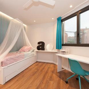 Imagen de dormitorio infantil de 4 a 10 años, contemporáneo, grande, con paredes blancas, suelo de madera en tonos medios y suelo marrón