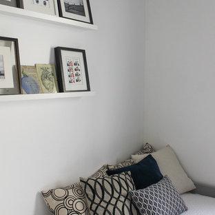 Esempio di una piccola cameretta per bambini industriale con pareti bianche, pavimento in laminato e pavimento marrone