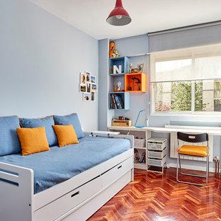 Modelo de dormitorio infantil contemporáneo, de tamaño medio, con paredes azules, suelo de madera en tonos medios y suelo marrón