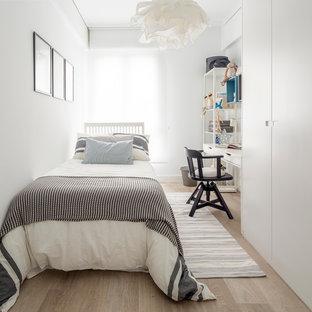 Imagen de dormitorio infantil de 4 a 10 años, escandinavo, de tamaño medio, con paredes blancas y suelo de madera en tonos medios