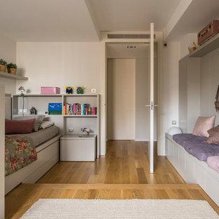 Ejemplo de dormitorio infantil actual con paredes blancas, suelo de madera en tonos medios y suelo marrón