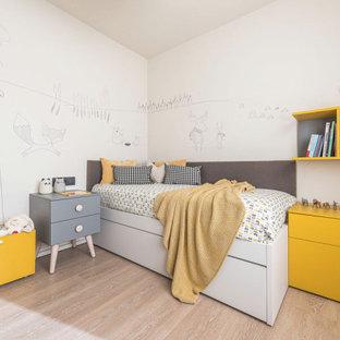 Ispirazione per una cameretta per bambini da 4 a 10 anni design di medie dimensioni con pareti bianche, parquet chiaro, pavimento beige e carta da parati