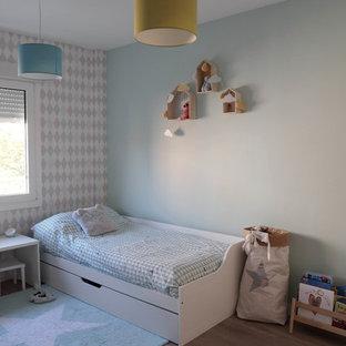 Ejemplo de dormitorio infantil minimalista con paredes azules, suelo laminado y suelo marrón