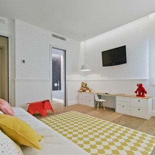 Diseño de habitación infantil unisex actual, de tamaño medio, con escritorio, paredes blancas, suelo marrón y suelo de madera en tonos medios