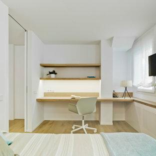 Ejemplo de dormitorio infantil contemporáneo, de tamaño medio, con escritorio, paredes blancas y suelo de madera clara