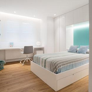 Modelo de dormitorio infantil actual, grande, con paredes blancas, suelo de madera en tonos medios y suelo beige